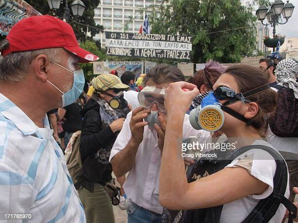 Greek protesters wearing improvised gas masks argue politics in an interlude between tear gas attacks by riot police in Athens.