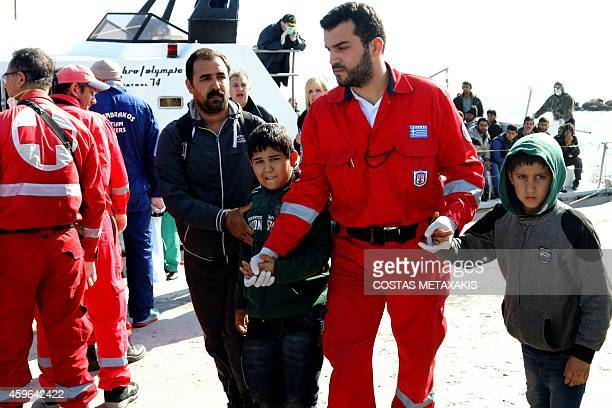A Greek Red Cross member escorts two children as migrants arrive at the Cretan port of Ierapetra on November 27 2014 Around 700 migrants aboard a...