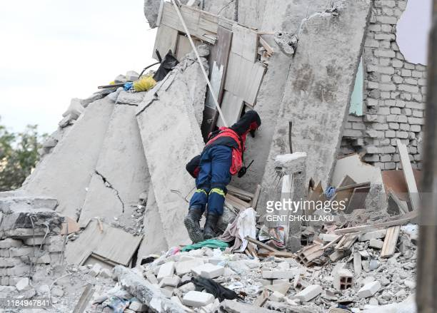 Greek rescue worker searches for survivors through the rubble of a collapsed building on November 27, 2019 in Thumane, northwest of the capital...