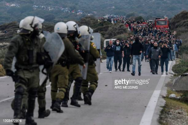 Greek riot police face demonstrators during protests against the construction of a new controversial migrant camp near the town of Mantamados on the...