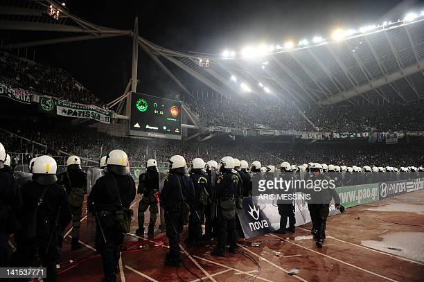 Greek riot police line up in front of Panathinaikos supporters during a Greek Super League football game against Olympiakos at the Athens Olympic...