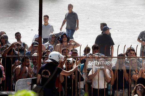 Greek riot police officer stands guard as migrants and refugees wait to be registered at the national stadium on August 12 2015 in Kos Greece Greek...