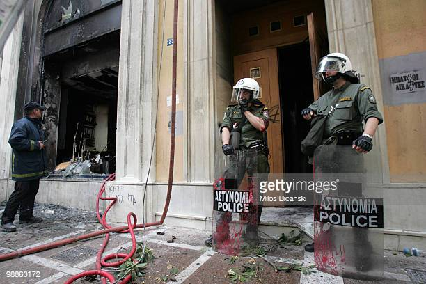 Greek riot police secure the entrance of the Marfin Egnatia Bank where 3 people died after protesters set fire to the building on May 5 2010 in...