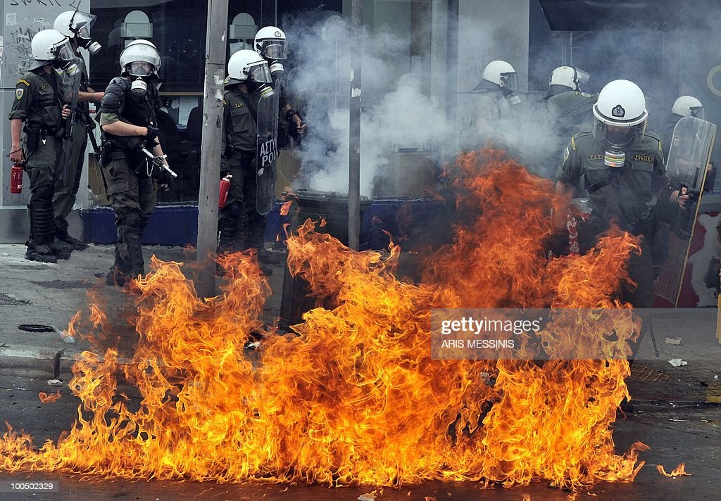 A Greek riot policeman runs away from a fire after a group set fire with a Molotov cocktail during clashes near the Parliament building in the center of Athens on May 5, 2010. A nationwide general strike gripped Greece in the first major test of the socialist government's resolve to push through unprecedented austerity cuts needed to avert fiscal meltdown.Three people were killed in a firebomb attack on a bank in central Athens and around 20 people were being evacuated from the building, police said.