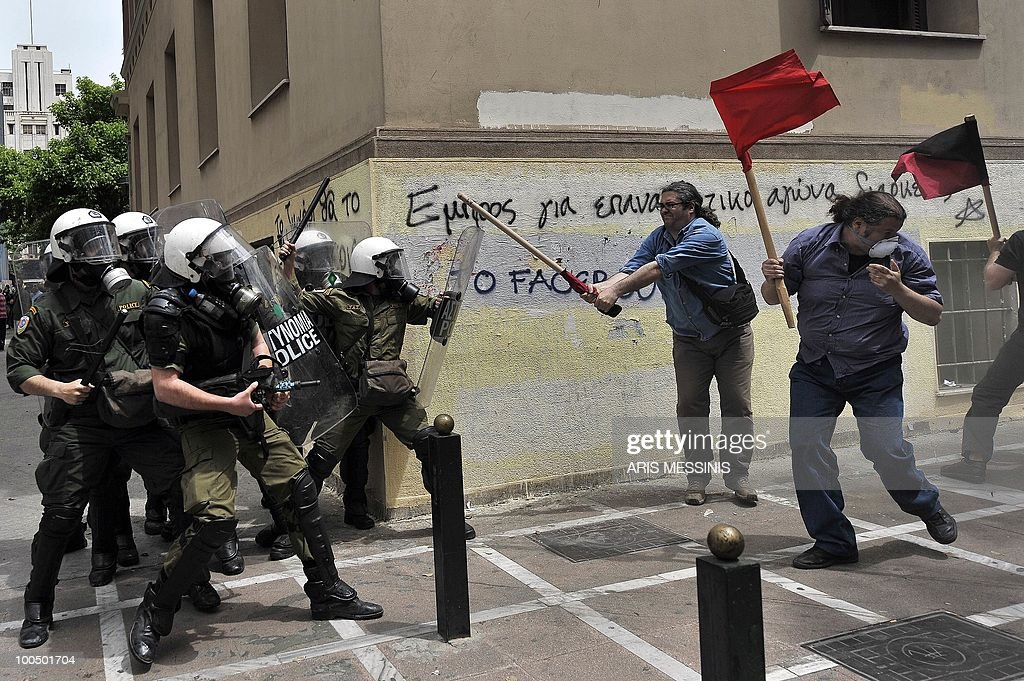 Greek riot policemen clash with protestors in the center of Athens on May 5, 2010. A nationwide general strike gripped Greece in the first major test of the socialist government's resolve to push through unprecedented austerity cuts needed to avert fiscal meltdown. Three people were killed in a firebomb attack on a bank in Athens and around 20 people were being evacuated from the building, police said.