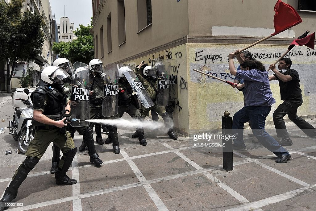 Greek riot policemen spray tear gas and