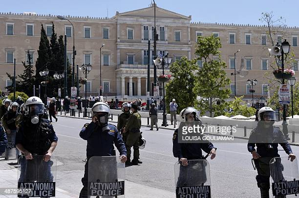 Greek riot policemen stand guard during a May Day rally in central Athens on May 1 2014 Tens of thousands of people across the globe hit the streets...