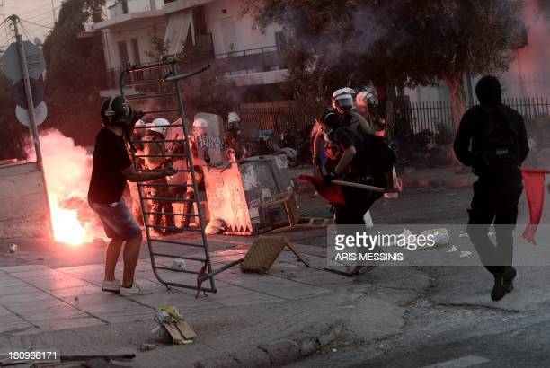 Greek riot policemen take position as protesters set up a makeshift barricade during clashes in Athens on September 18 2013 Clashes broke out between...
