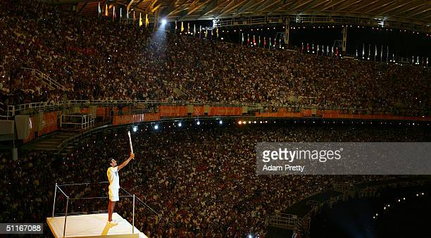 Greek sailor Nicolaos Kakalamanakis holds the Olympic torch after lighting the Olympic flame during opening ceremonies for the Athens 2004 Summer...