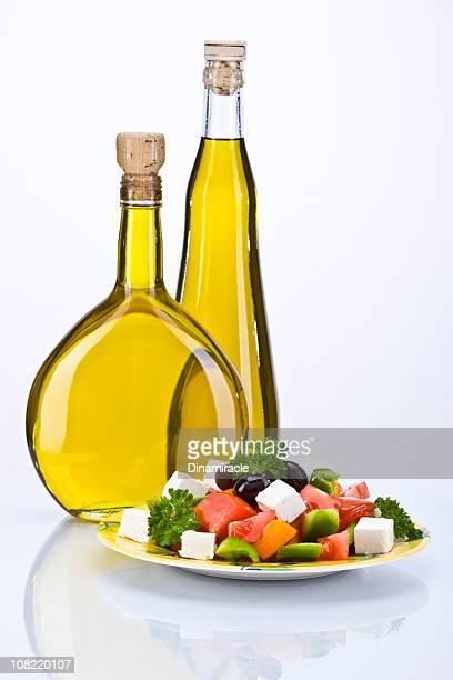 Ensalada griega y aceite de oliva en dos botellas