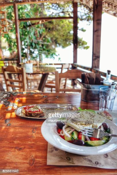 Greek salad on wooden table with glasses and plates