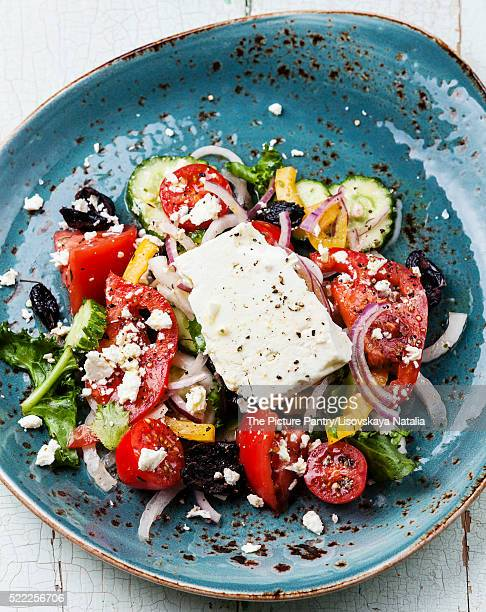 Greek salad with feta cheese and sun-dried olives on blue backgr