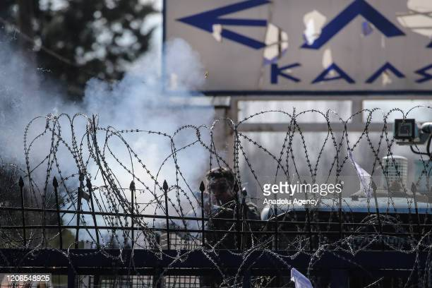 Greek security force member launches a tear gas canister towards asylum seekers waiting at the buffer zone located between the Kastanies and the...