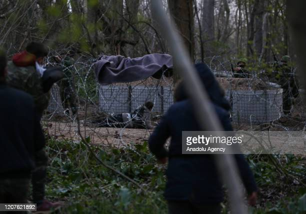 Greek security force members intervene in asylum seekers, waiting at the woodland between the Kastanies and the Pazarkule border gates, on March 18,...