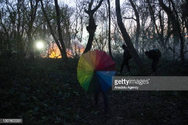 Greek security force members intervene in asylum seekers, waiting at the woodland between the Kastanies and the Pazarkule border gates, with tear gas...