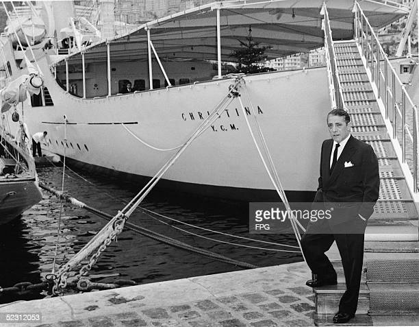 Greek shipping magnate Aristotle Onassis stands on a dock in front of his private yacht the 'Christina O' which he named after his daughter Christina...