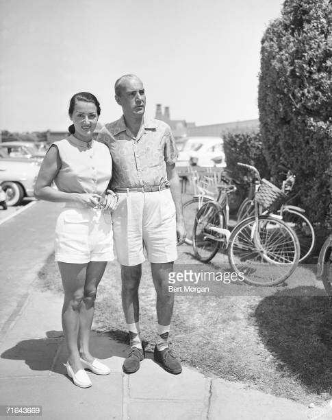 Greek shipping magnate Basil Goulandris and his wife Elise stand in shorts at the entrance of the Southampton bathing Corporation, Southampton, New...