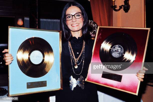 Greek singer Nana Mouskouri poses in September 1973 with her two gold discs for record sales.