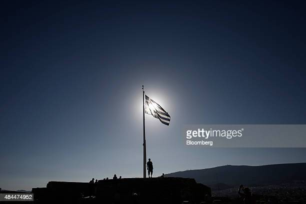 A Greek soldier stands beneath a Greek national flag following a morning flag raising ceremony on Acropolis Hill in Athens Greece on Wednesday Aug 19...
