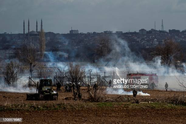 Greek soldiers and riot police officers stand stand amid clouds of tear gas at the Greece-Turkey border during clashes between migrants and riot...