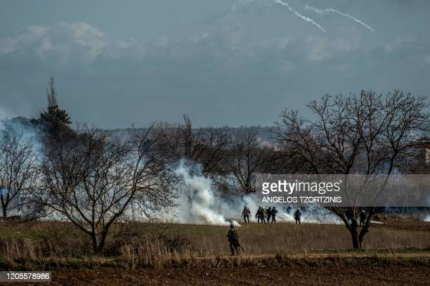Greek soldiers and riot police officers stand stand amid clouds of tear gas at the GreeceTurkey border during clashes between migrants and riot...