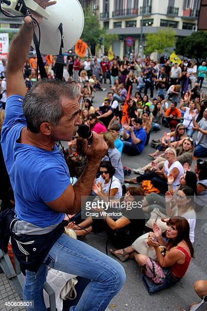 CONTENT] Greek teacher holding a megaphone in a dramatic pose addresses striking colleagues in protest over Greek government austerity reforms in...