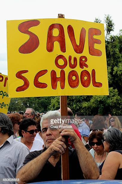 CONTENT] Greek teacher holding placard saying Save Our Schools during protest over austerity measures in education imposed by the government