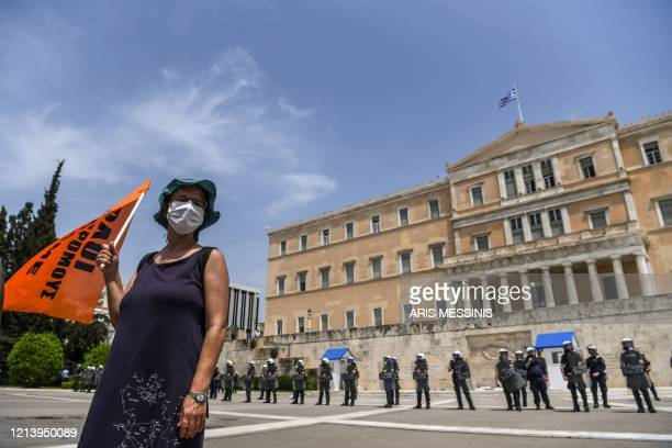 Greek teachers and students wearing protective face masks demonstrate in front of the Greek Parliament in central Athens on May 19 against the...
