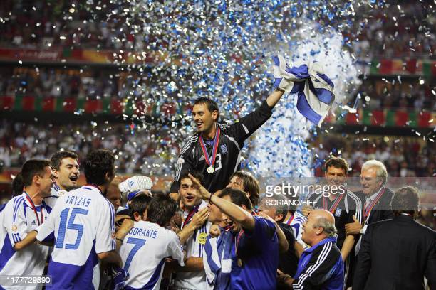 Greek team members hold the cup and celebrate, 04 July 2004 at the Luz stadium in Lisbon, at the end of the Euro 2004 final match between Portugal...