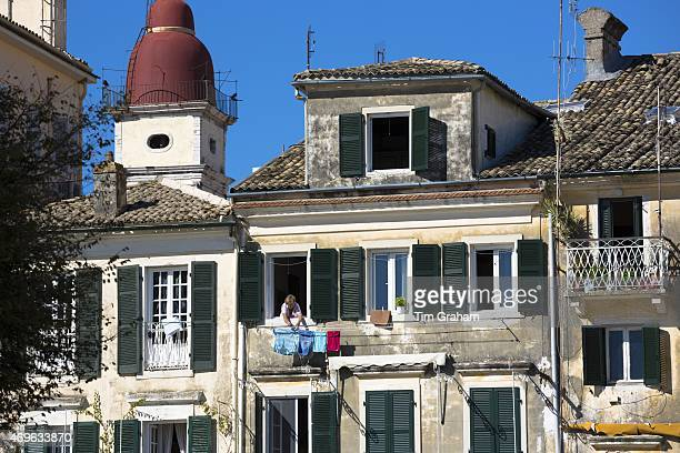 Greek woman hanging out washing on line from window of traditional apartment in Kerkyra Corfu Town Greece