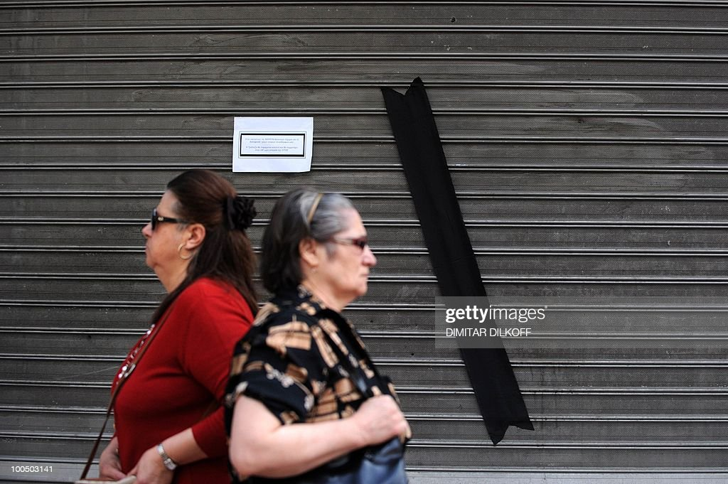 Greek women walk past a closed branch of the Marfin bank in the center of Athens on May 6, 2010. Greek bank workers walked off the job in a 24-hour strike Thursday to protest the deaths of three colleagues trapped in a bank torched by protesters during massive demonstrations against the government's new harsh austerity measures.