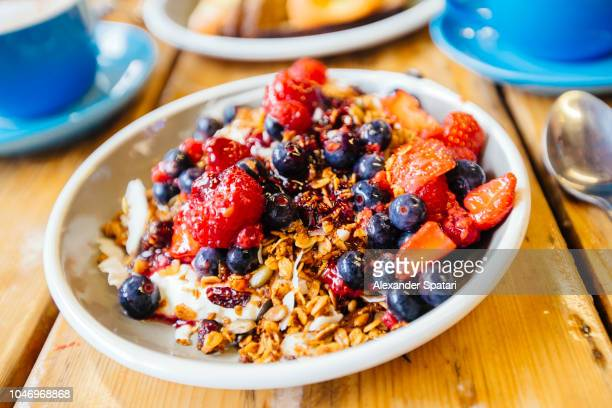 Greek yogurt with granola, blueberry and strawberry on the table close up