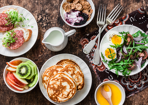 Greek yogurt with whole grain cereals and berry sauce, pancakes, arugula, cherry tomatoes, boiled eggs salad, kiwi, apples fruit, salami and cream cheese sandwiches on a wooden background, top view. Flat lay breakfast table 939461114