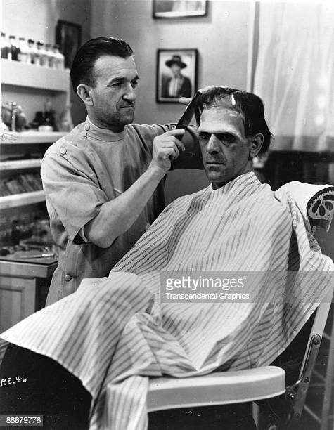 Greekborn American makeup artist Jack P Pierce applies makeup and combs the hair of British actor Boris Karloff for Karloff's role as the monster in...