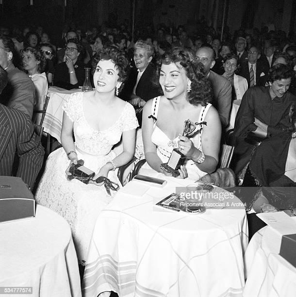 Greekborn Italian actress Yvonne Sanson and Italian actress Gina Lollobrigida smiling holding the Vittorie cinematografiche awards Rome 10th June 1954