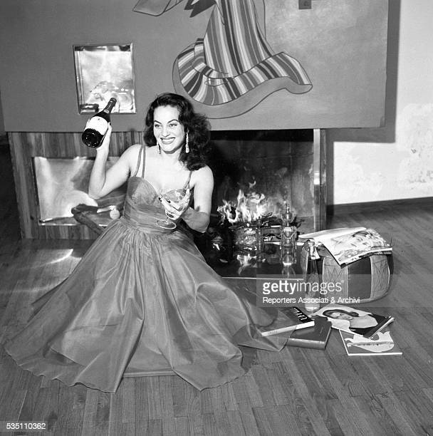 Greekborn Italian actress Yvonne Sanson drinking a toast to the New Year in her villa on the Appian Way Rome December 1955