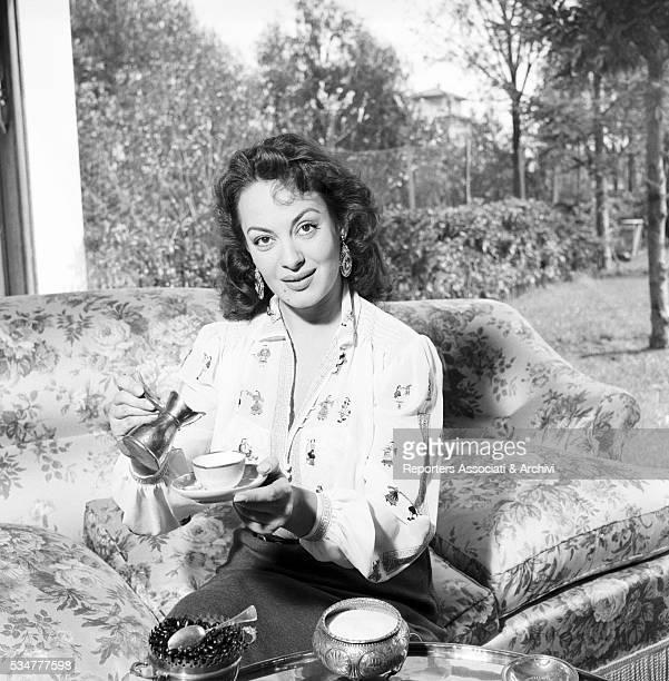 Greekborn Italian actress Yvonne Sanson having her breakfast on the sofa in her villa on the Appian Way in Rome 1952