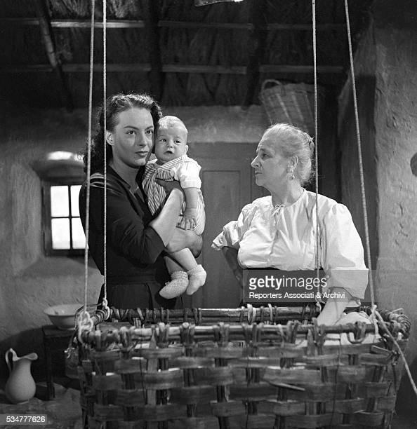 Greekborn Italian actress Yvonne Sanson holding a baby beside Italian actress Teresa Franchini in the film Nobody's Children 1951