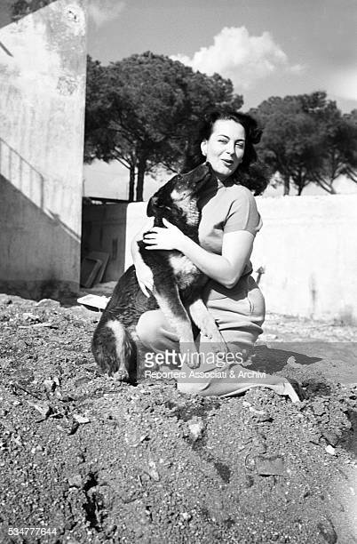 Greekborn Italian actress Yvonne Sanson hugging her dog 1951
