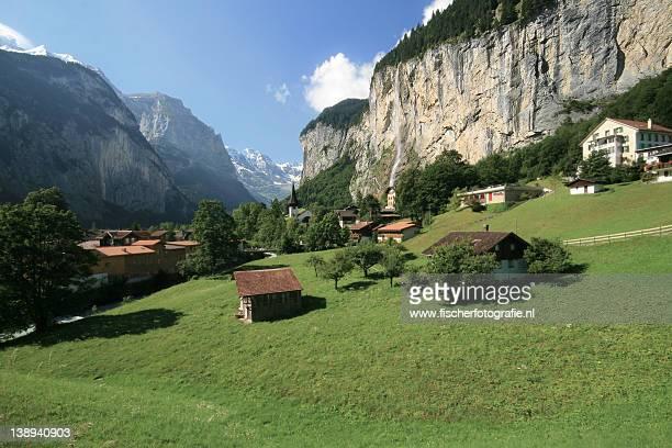 green alpine fields with high waterfalls - lauterbrunnen - fotografias e filmes do acervo