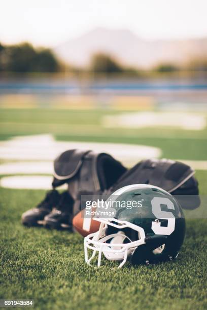 green american football helmet on playing field - michigan state university football stock pictures, royalty-free photos & images