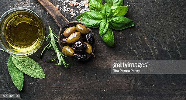Green and black Mediterranean olives in old cooking spoon with olive oil and herbs