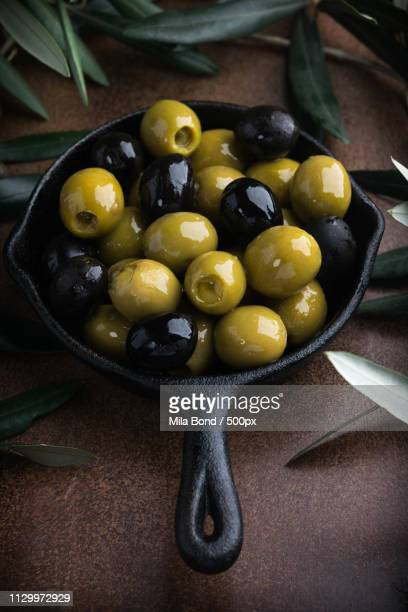 green and black olives with italian traditional snack grissini, rustic wooden board copy space - green olive fruit stock pictures, royalty-free photos & images