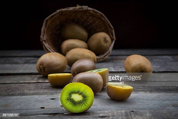 Green and golden kiwis, basket on wood