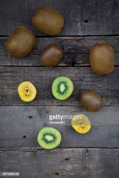 Green and golden kiwis on wood