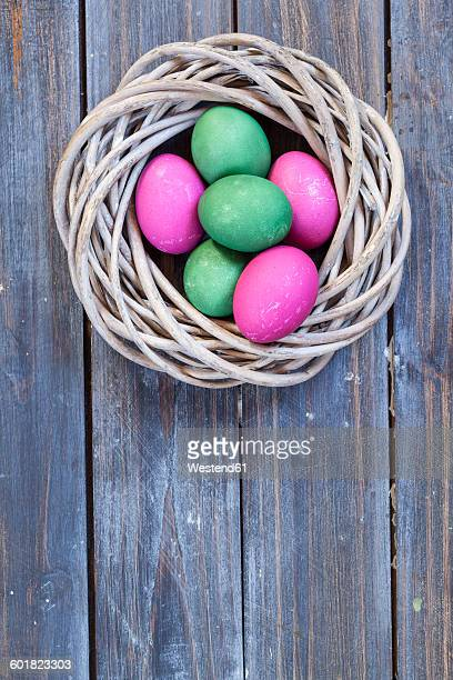 Green and pink Easter eggs in nest