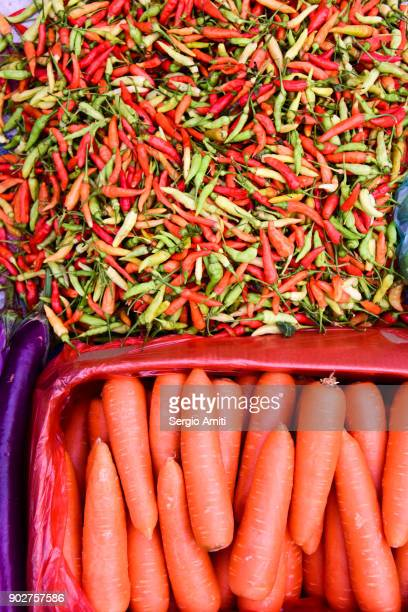 Green and red chillies and carrots on sale in Laos