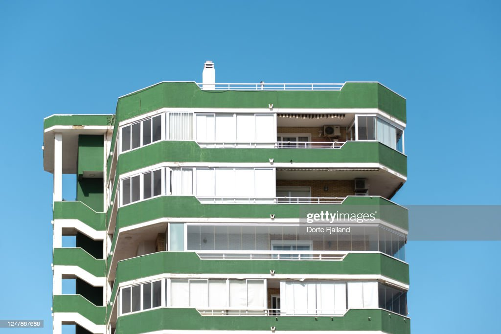 Green and white apartment building against a blue sky : Foto de stock
