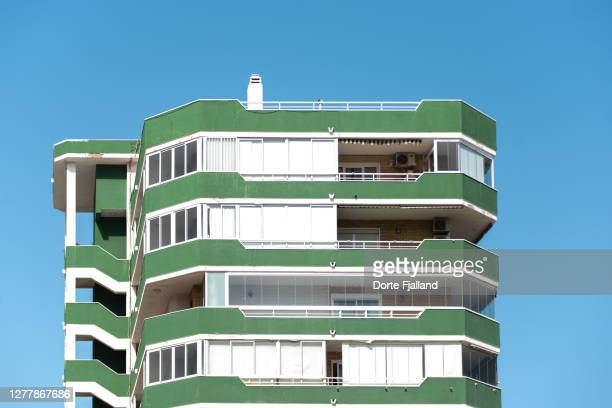 green and white apartment building against a blue sky - dorte fjalland fotografías e imágenes de stock