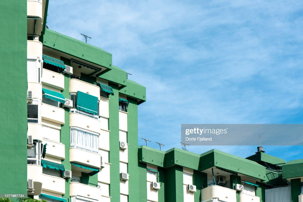 Green and white apartment buildings against a blue sky on a sunny day : Foto de stock